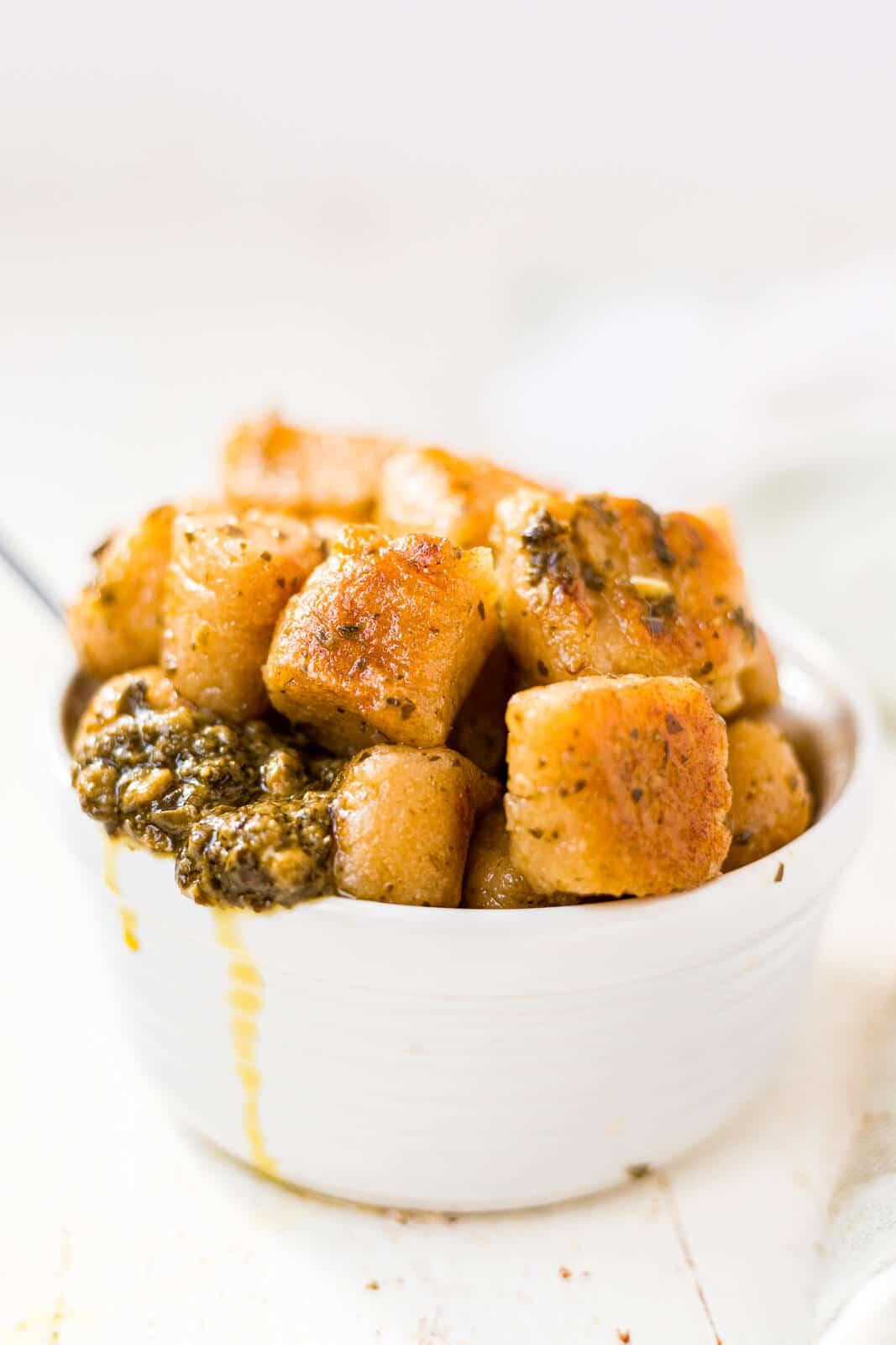 homemade cauliflower gnocchi piled into a white bowl tossed in pesto