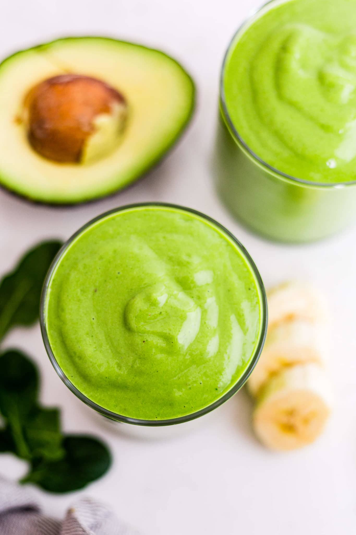 the top of a green smoothie in a glass with spinach, bananas and avocado around it