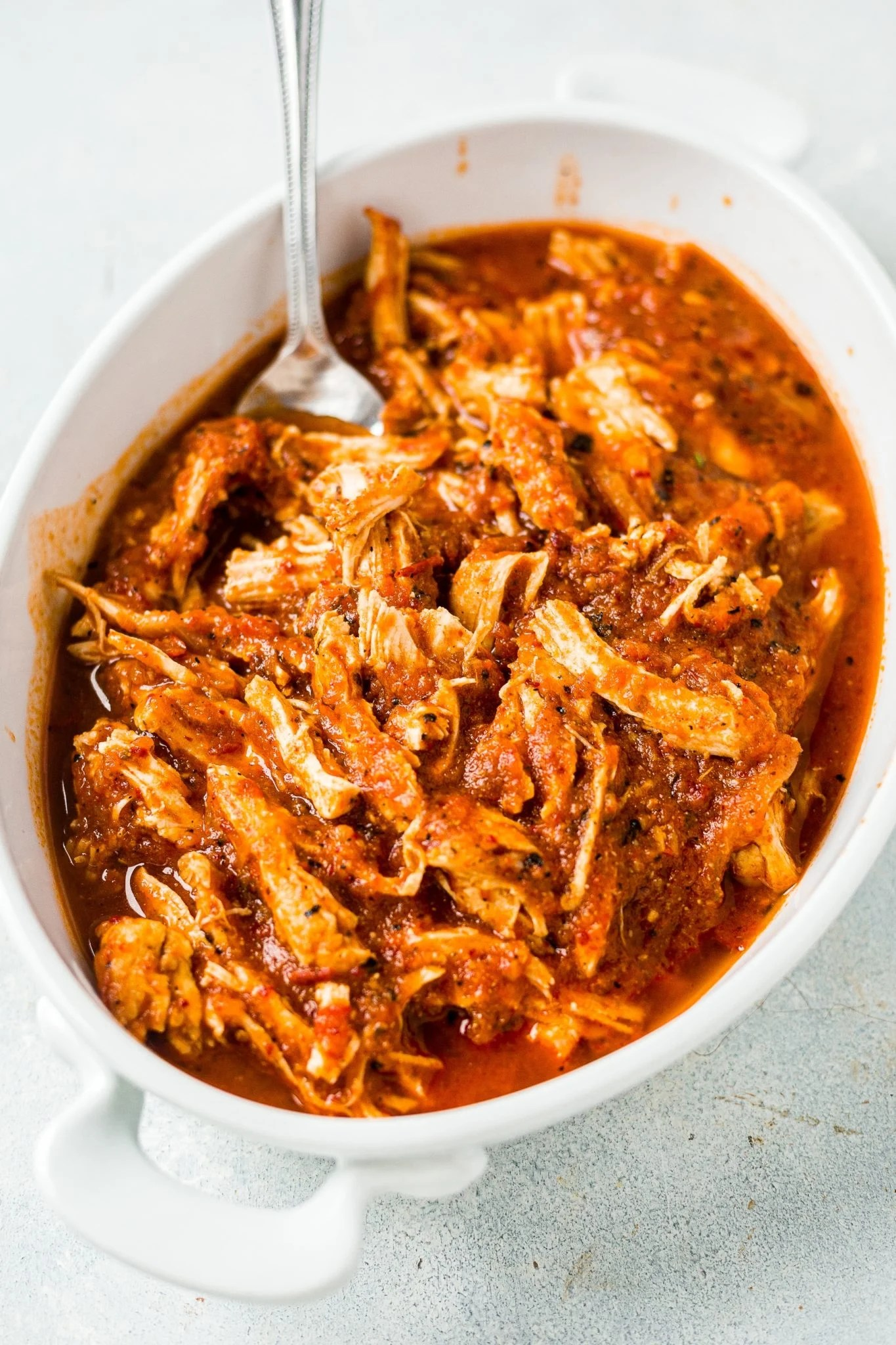chicken tinga in a white serving dish with a fork