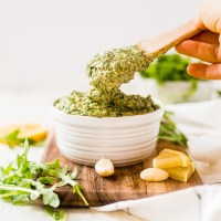 wooden spoon scooping out a serving of fresh arugula pesto from a white serving bowl on a wooden cutting board