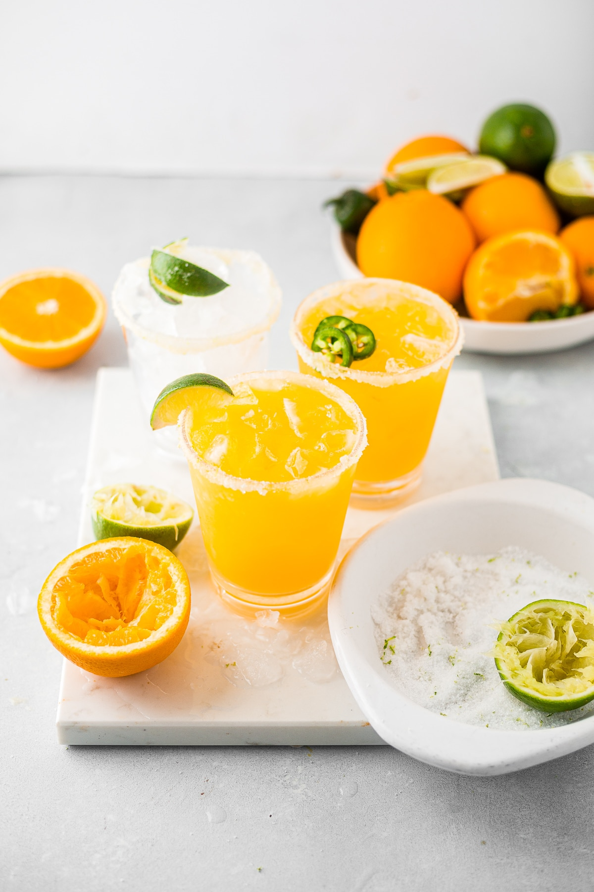 two mango margaritas on a marble slab garnished with salt and limes and surrounded by fresh oranges