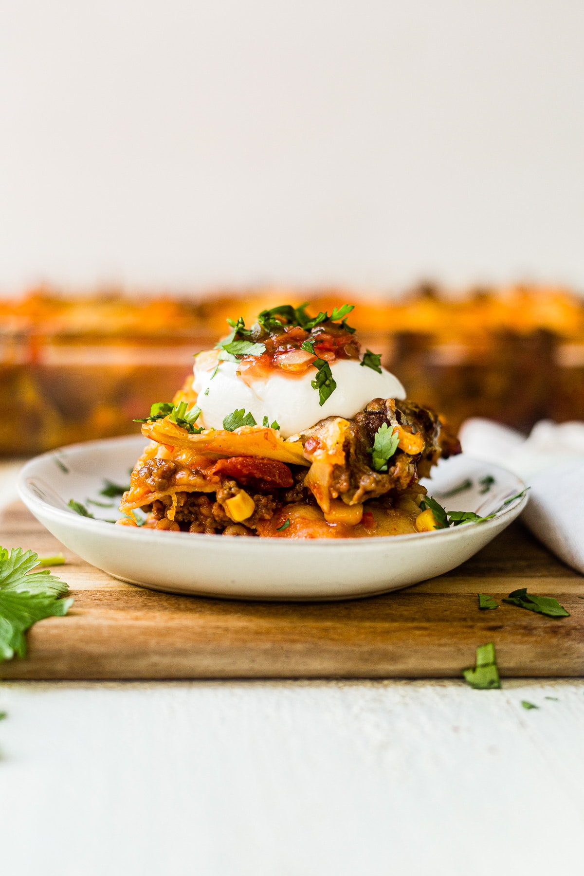 a piece of mexican lasagna on a white plate topped with sour cream, salsa and avocado