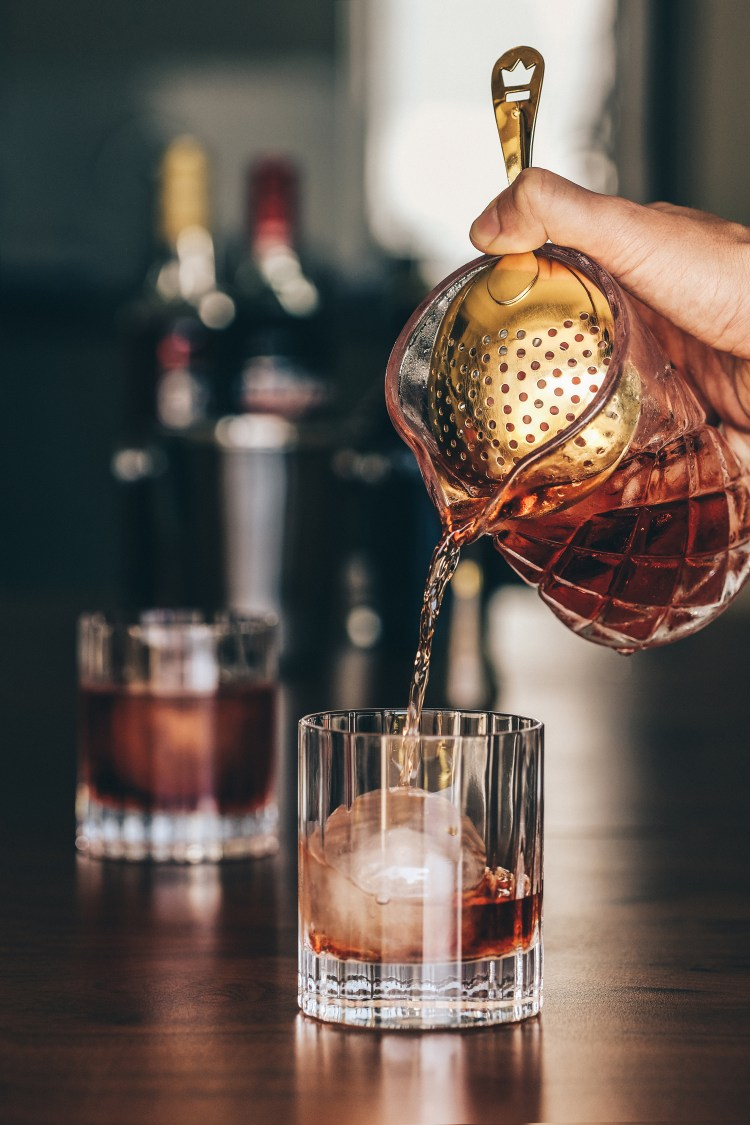 Negroni-being-poured-from-stirring-glass