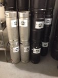 Small kegs stacked next to a cold storage unit.