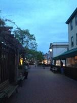Ugly Mug employee stands under the awning along the Washington Street Mall.