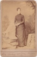 You are looking at a full length cabinet photograph portrait of a Victorian era woman standing rather incongruously next to a fake boulder with a woodland background. The lady is wearing a typical dark dress ensemble from the 1880's: corseted jacket with brooch at the throat, pleated underskirt and probably a modified bustle. The corset is only a hint at what the expectations of the female body were at the time.