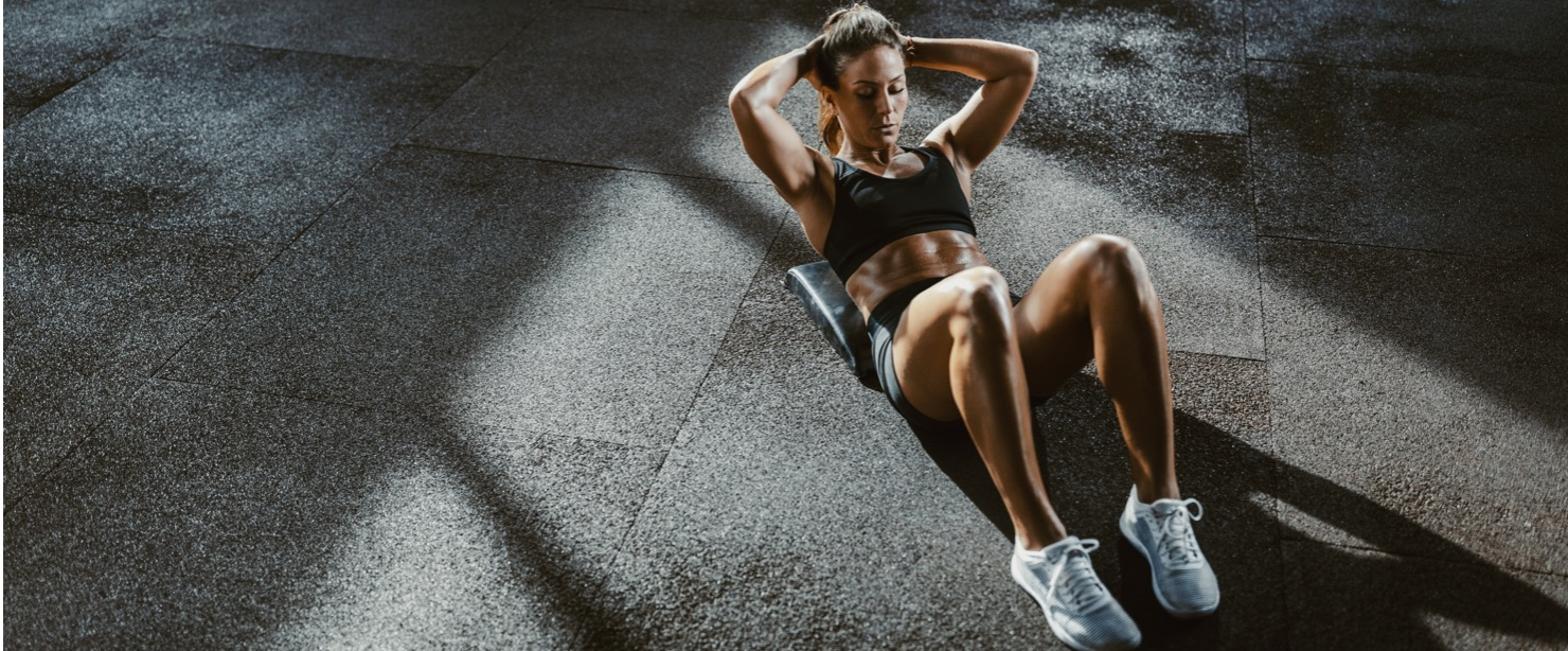 fit woman doing situps on the floor