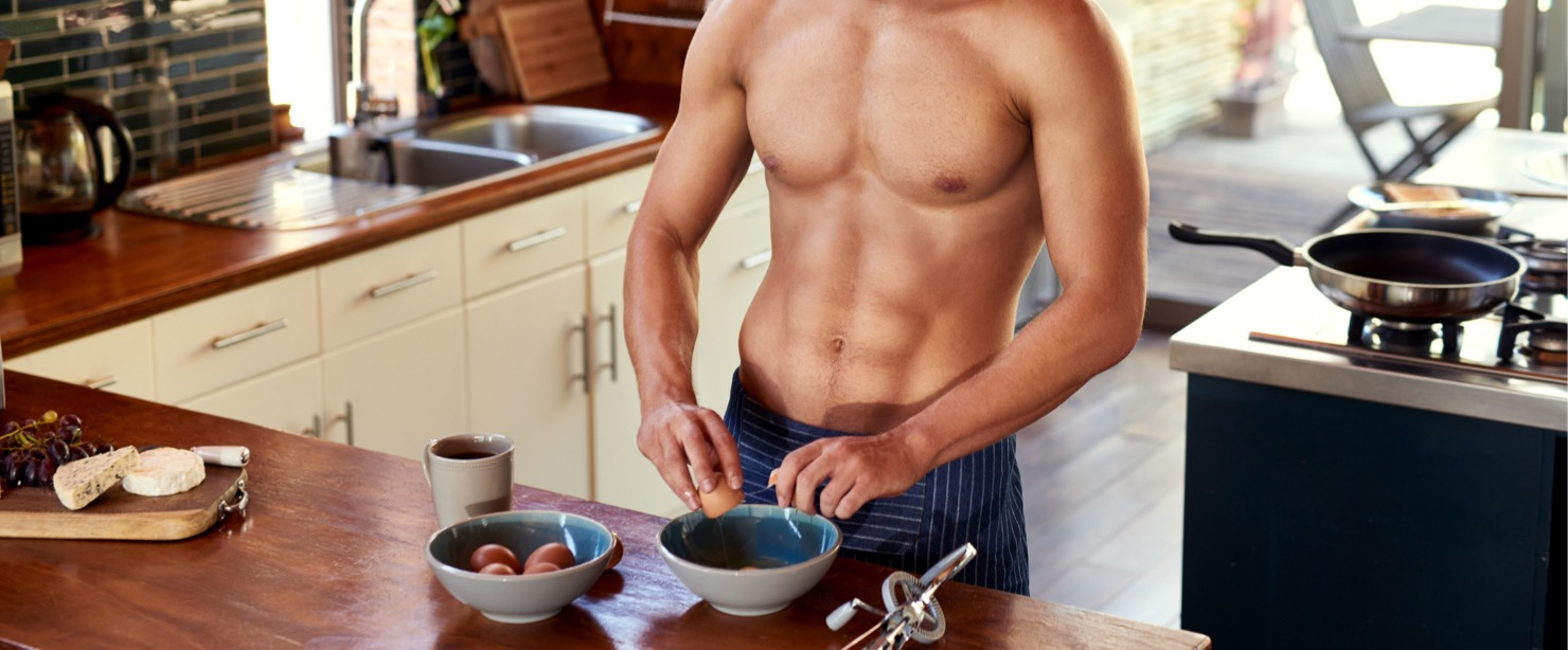 guy with abs making eggs in the kitchen