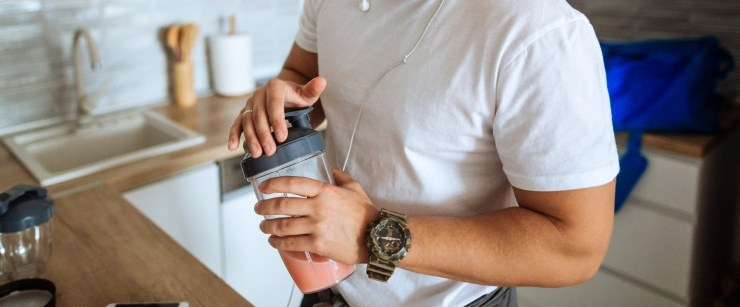 fit man holding protein shake