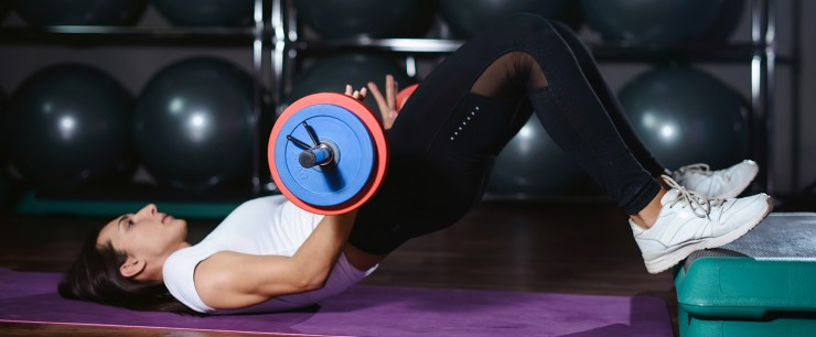strong woman doing glute bridge exercise with small barbell