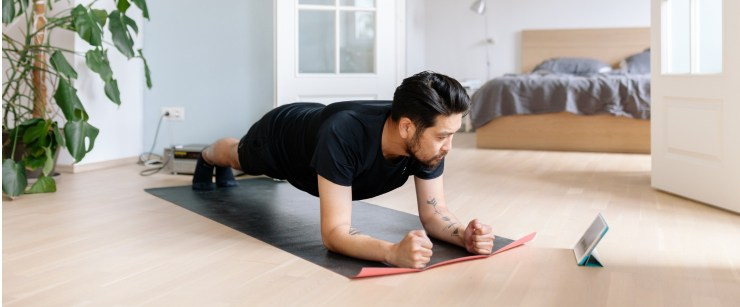 man doing plank while watching home workout video