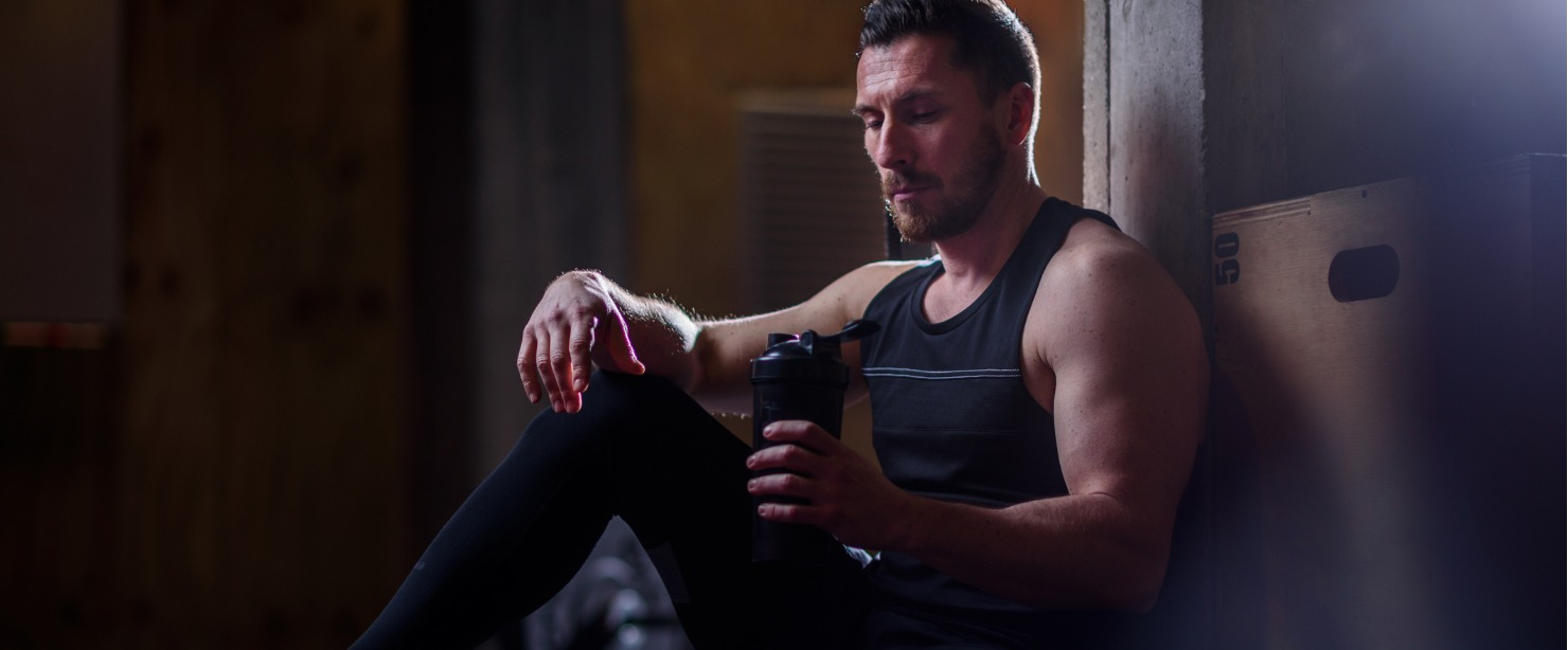 fit man drinking pre-workout shaker bottle at the gym