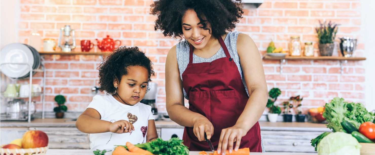 mother and daughter cutting carrots in the kitchen