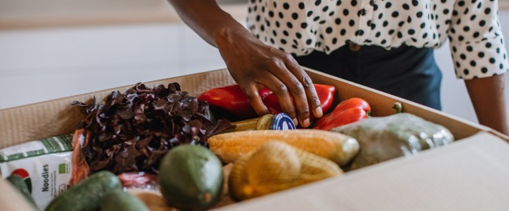 woman unloading a box of groceries at home