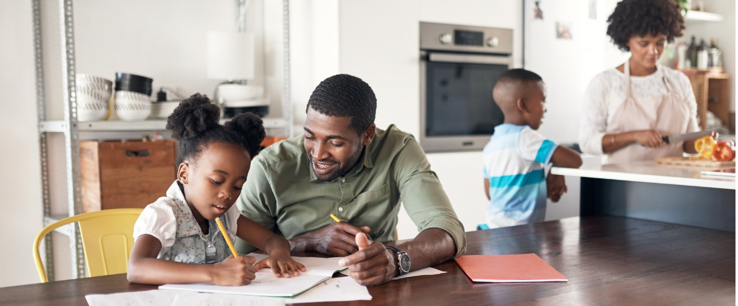 dad helping daughter with schoolwork while mom and son cook