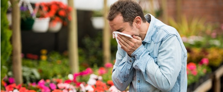 man sneezing from allergies while at a greenhouse