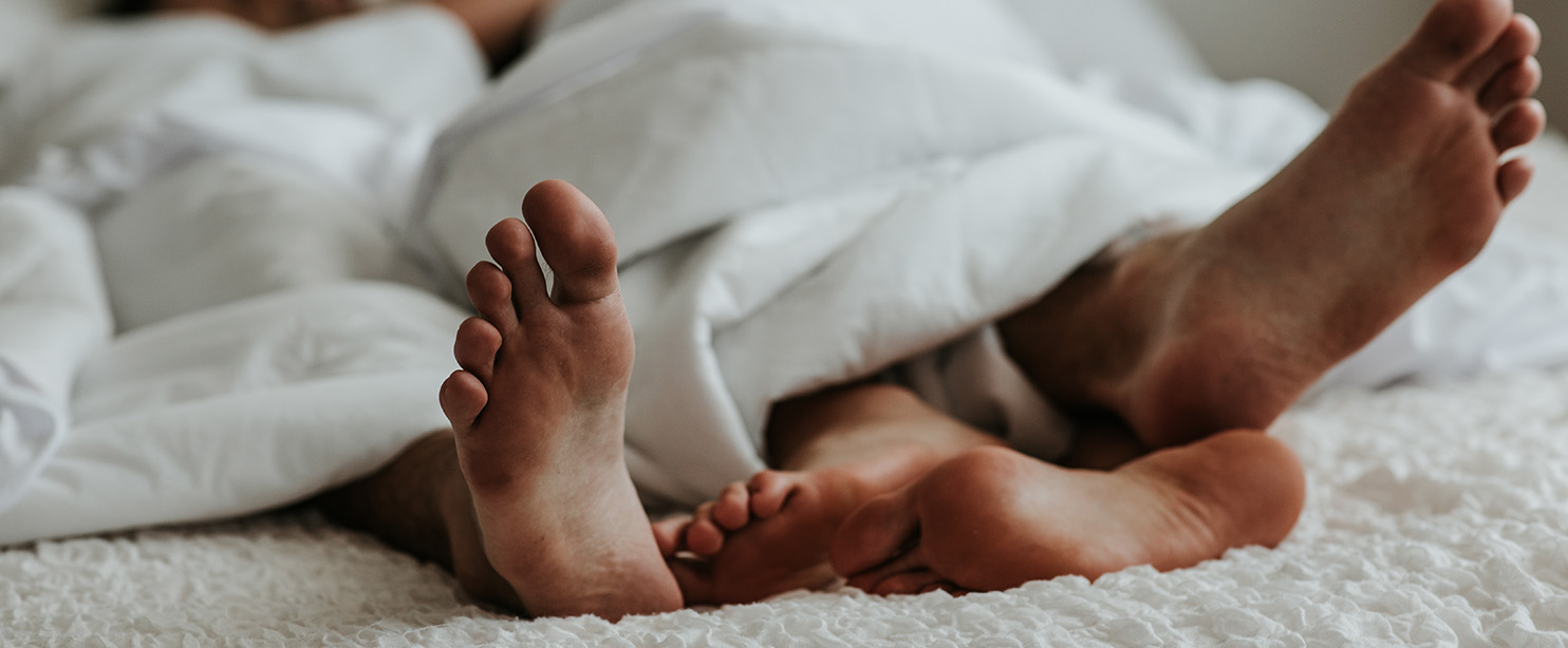 feet of happy couple in bed