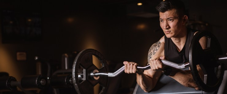 young fit guy performing barbell biceps curls