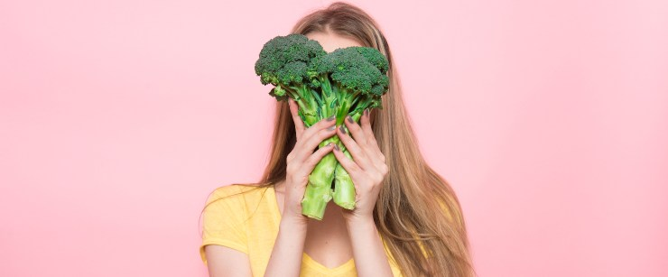 healthy foods and digestive issues: young woman holding broccoli in front of face on pink background