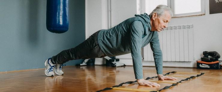 older man doing plank at home