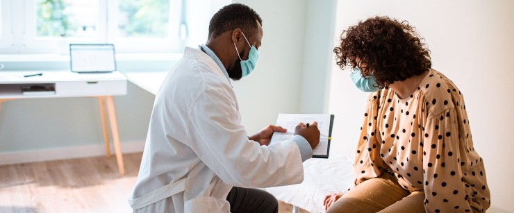 how to detect breast cancer early: woman with doctor in office