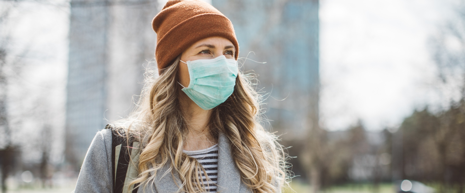 mascne: woman outside in beanie and face mask