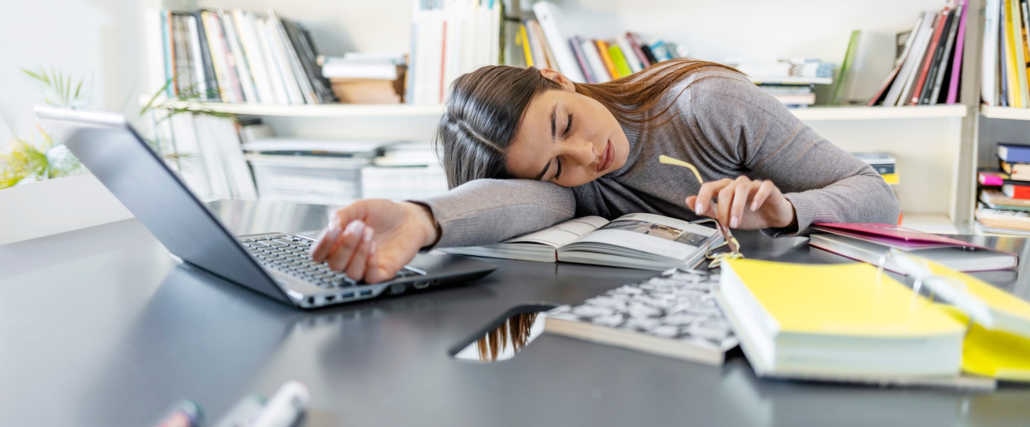 young fatigued woman falling asleep working at desk