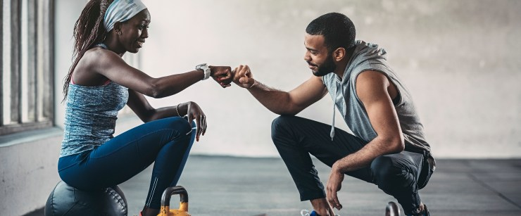 personal trainer and client fist bumping after workout