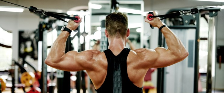 carnitine: muscular man using cable machine