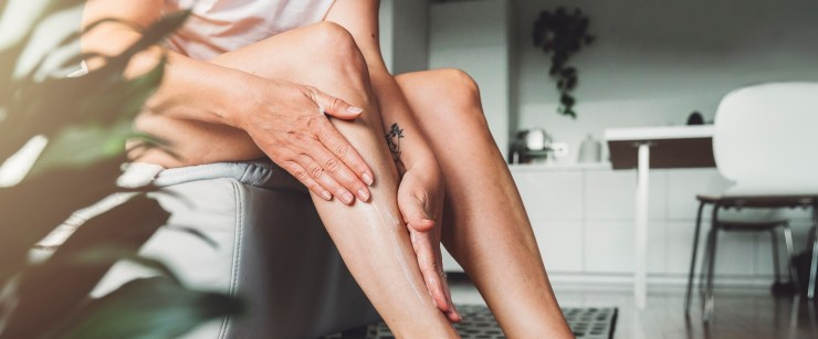 topical CBD products: woman applying lotion to legs