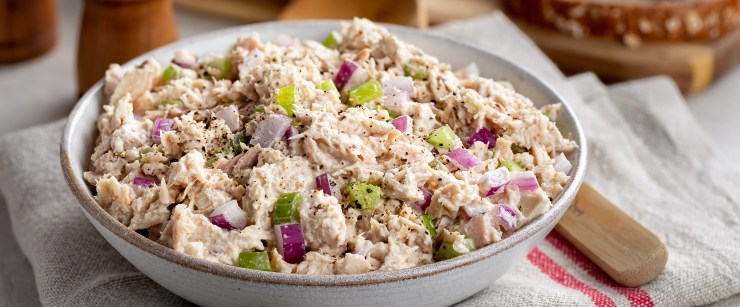 Tuna salad in a bowl on a napkin with makings for sandwiches in background