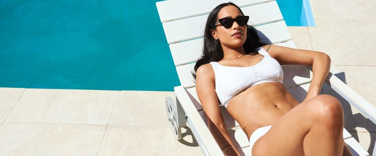 messing with collagen production: woman tanning outside near pool