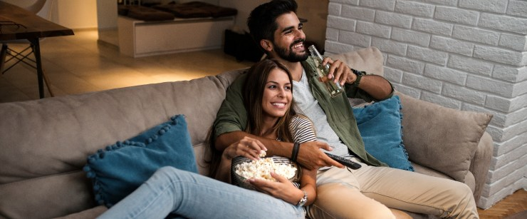 messing with your microbiome, couple on the couch watching tv and snacking