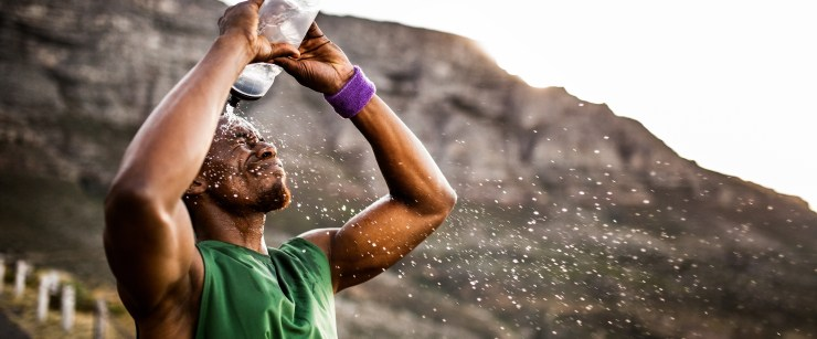 man squirting himself with water after workout