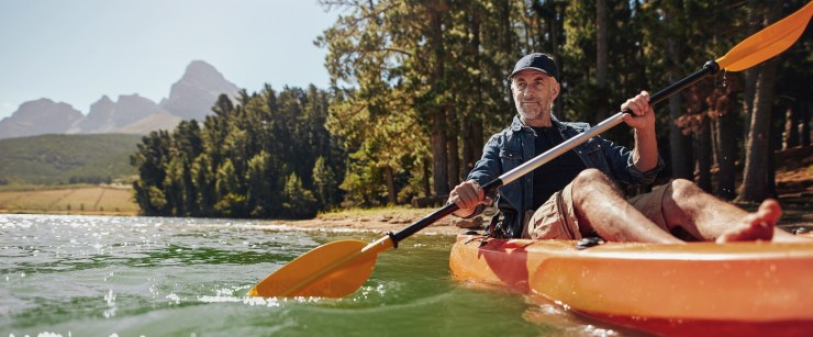 ways to support healthy cholesterol: older man kayaking on lake