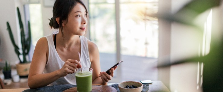social media health guru: young woman drinking green smoothie with phone