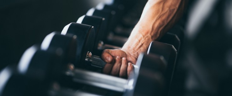 bodybuilding strategies: muscular hand picking up dumbbell