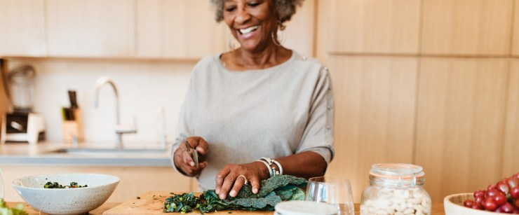 nutrients older adults need more of: older woman cutting kale in kitchen