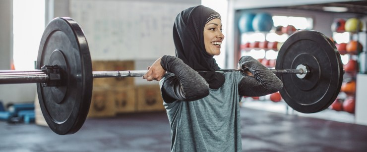 lighter weights: woman lifting barbell on fronts of shoulders