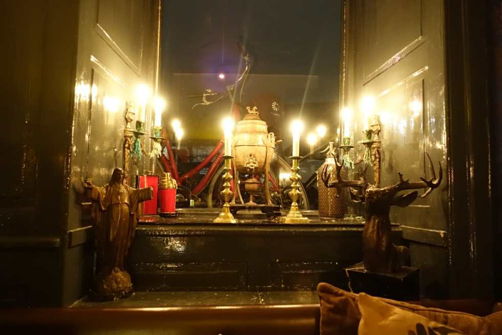 An eclectir decor of candles and random statues in the window