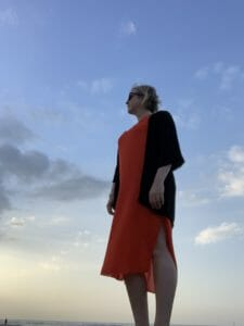 Katie on the beach wearing a longer orange dress with black cover up on top to cover shoulders and arms