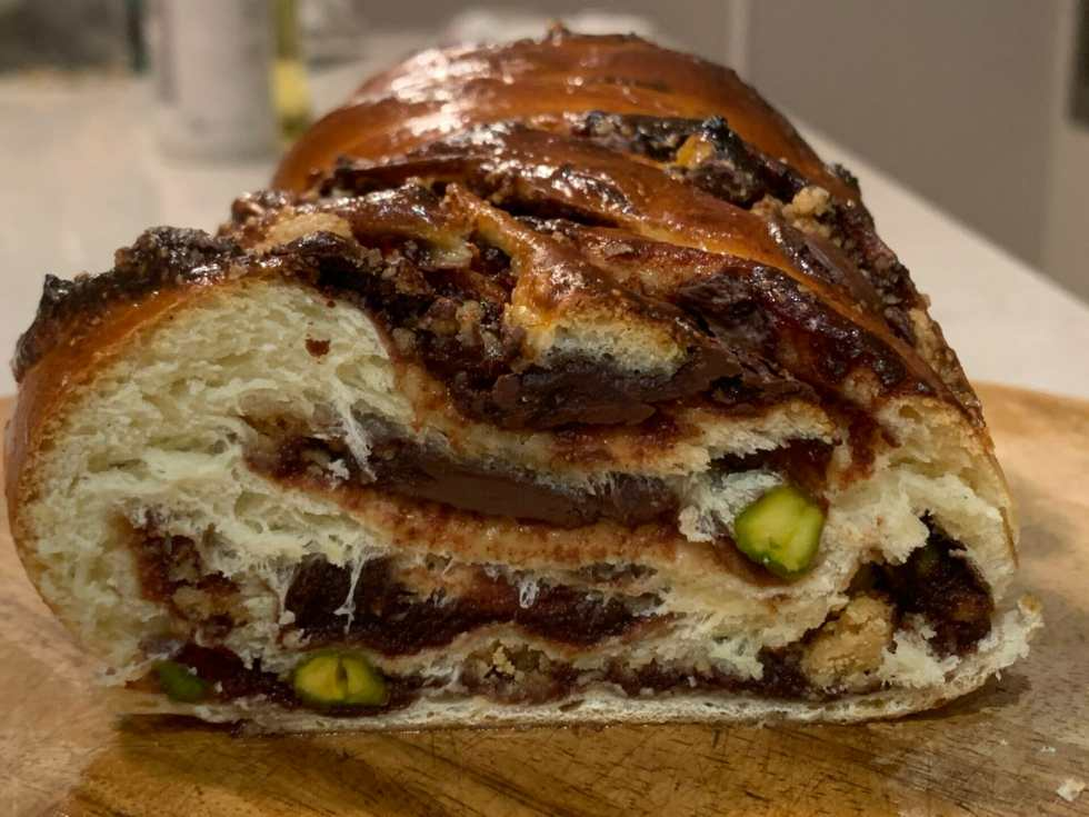 Cut open baked babka, showing date and chocolate and pistachios