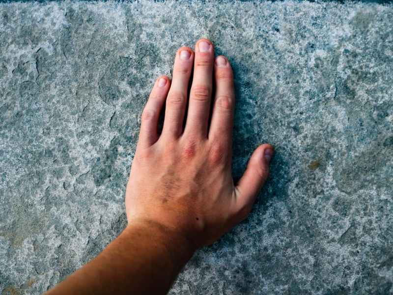 left human hand on grey surface