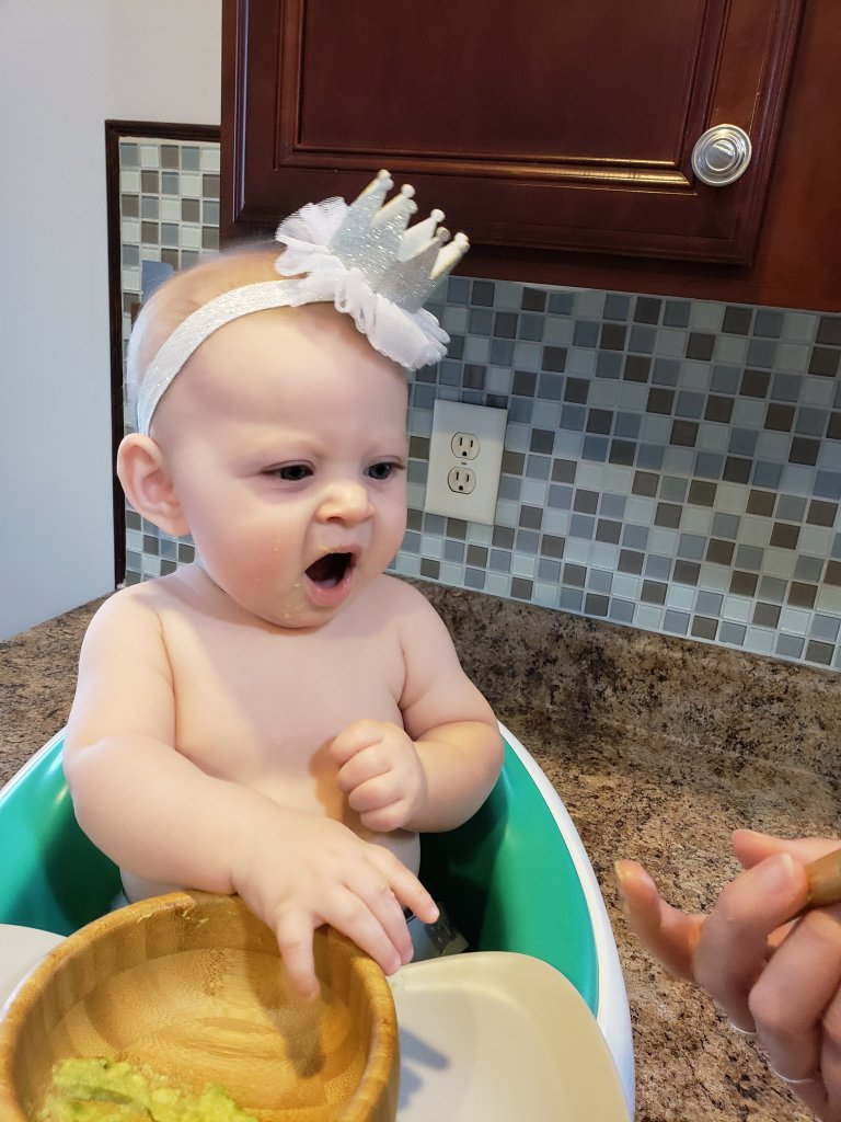 Child sitting in high chair with wooden bowl trying her first food