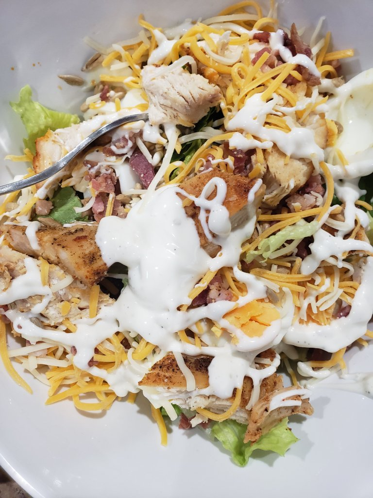 White bowl filled with chicken cheese salad and dressing