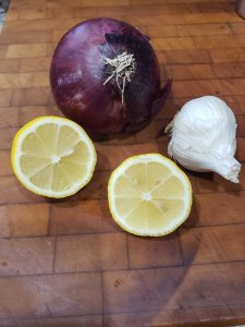 cutting board with sliced lemon garlic and red onion