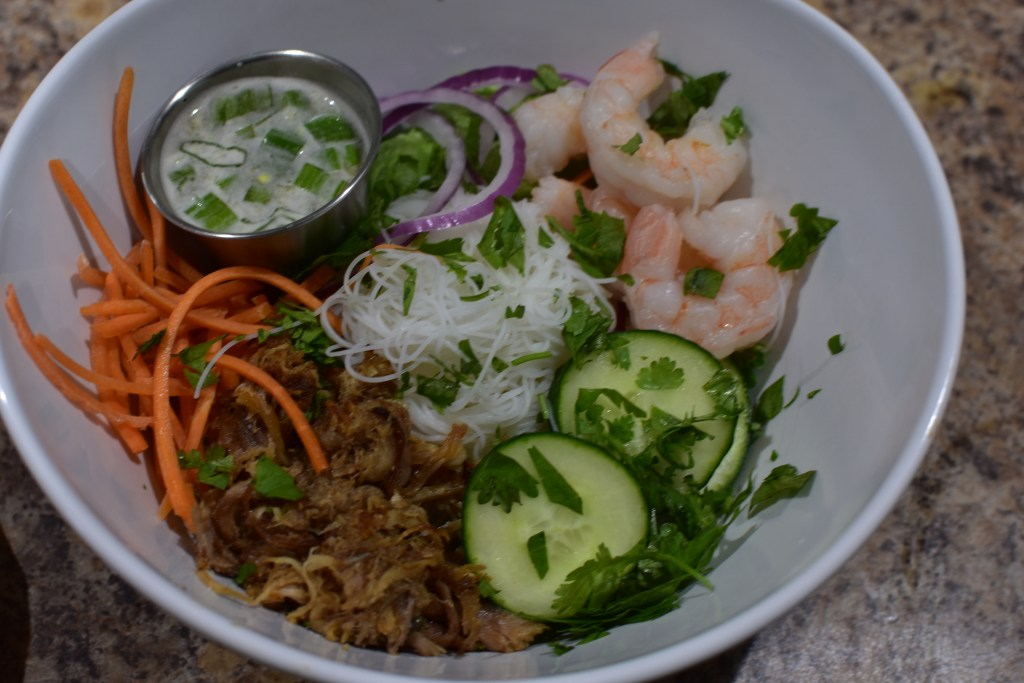 white bowl filled with shredded carrots, sliced cumber, sliced onion, rice noodles, shrimp and sauce in stainless steel saucer.