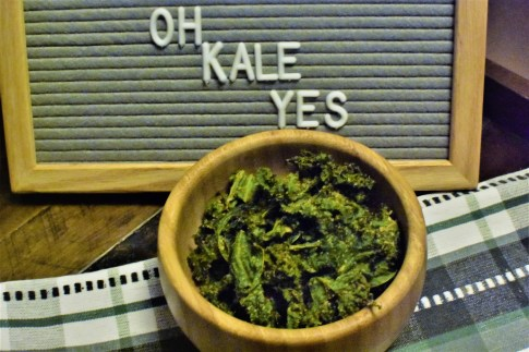a wooden bowl with kale chips and a sign saying oh kale yes