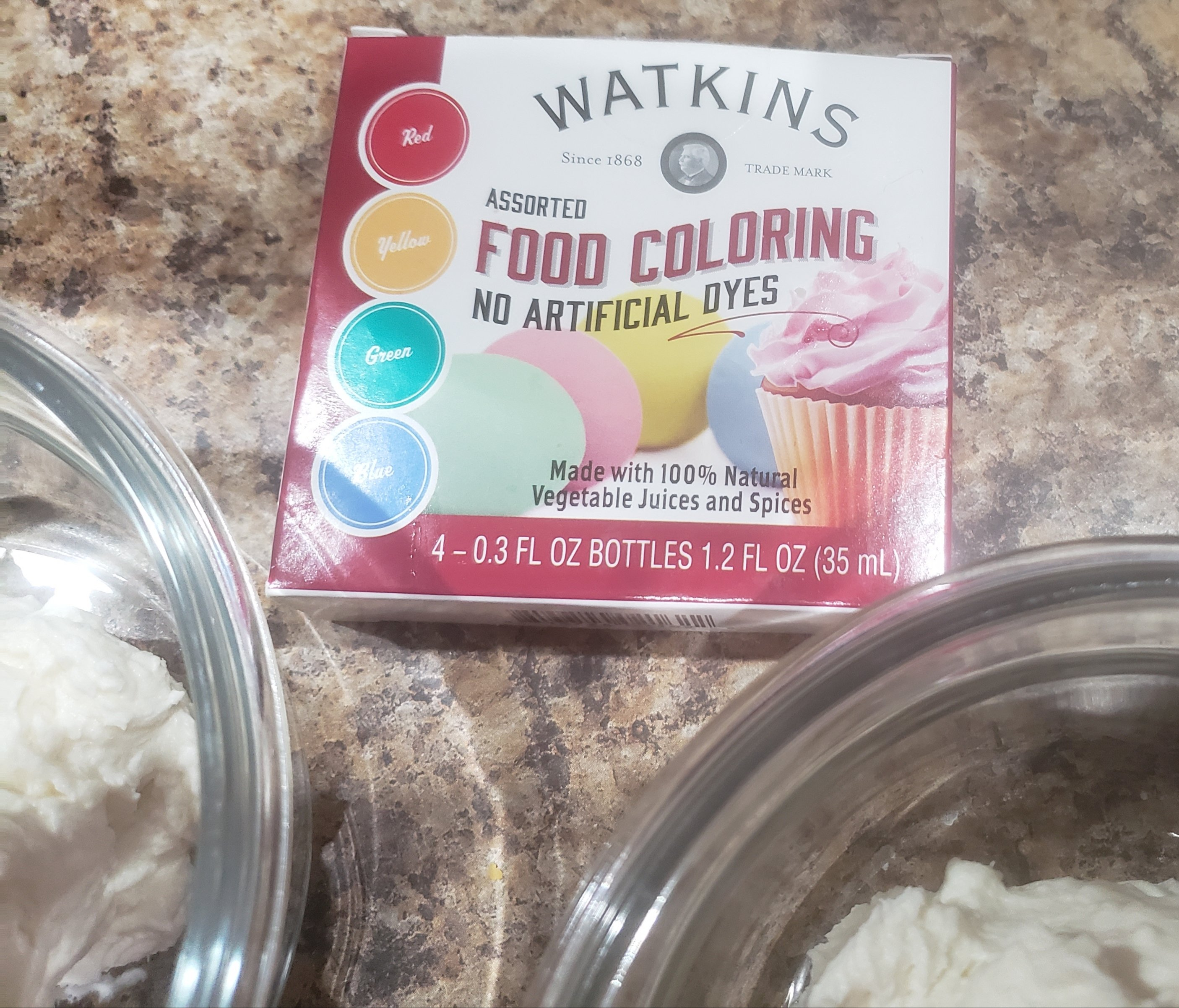 two glass bowls of frosting with food coloring package