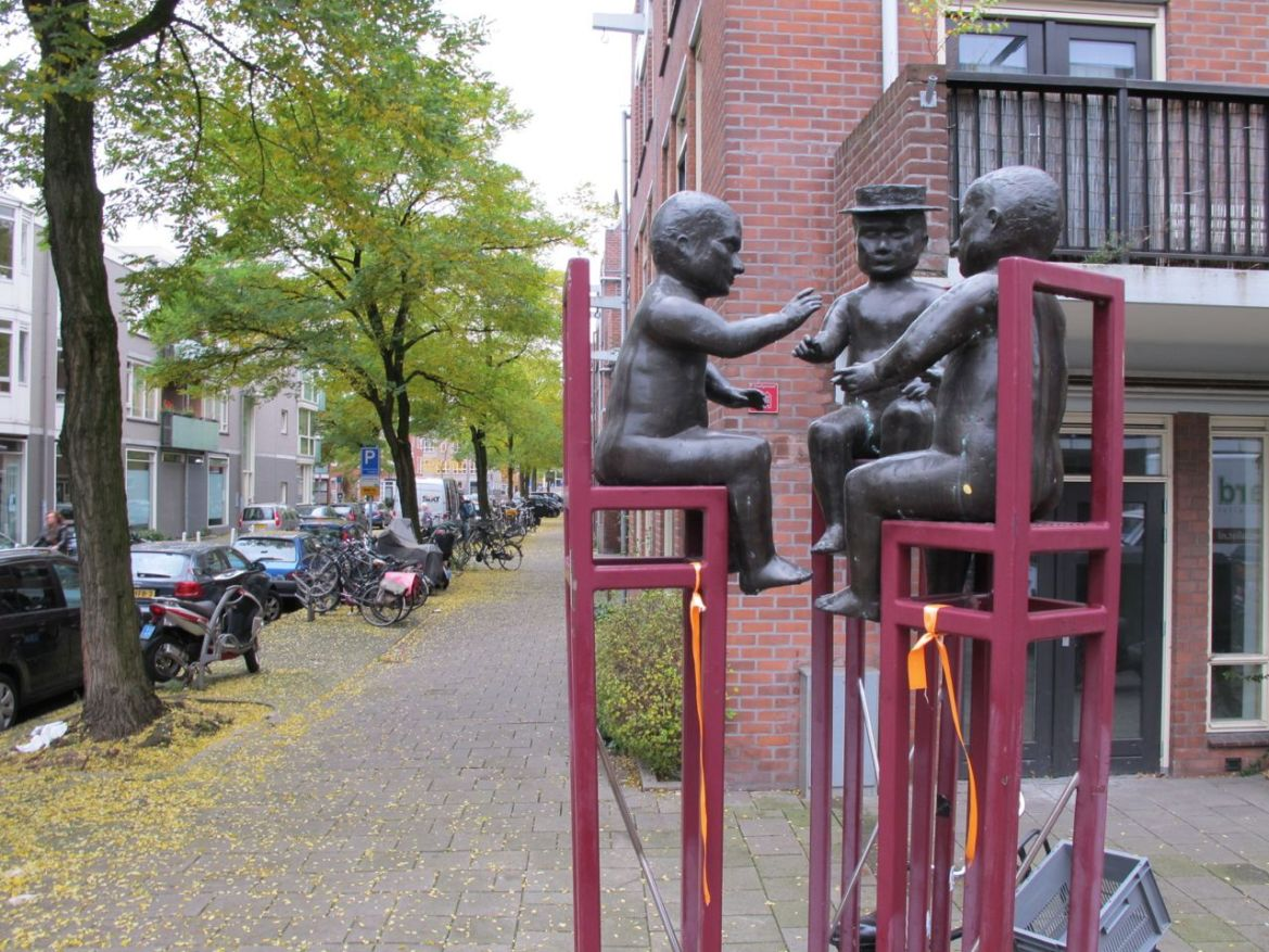 Three men in conversation, at Ten Katestraat, Amsterdam